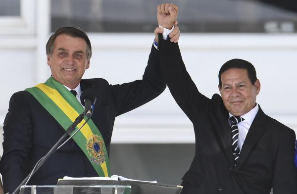 O novo presidente do Brasil, Jair Bolsonaro, e o novo vice-presidente, general Hamilton Mourão, erguem as mãos após discurso no parlatório do Palácio do Planalto — Foto: Evaristo Sá/AFP