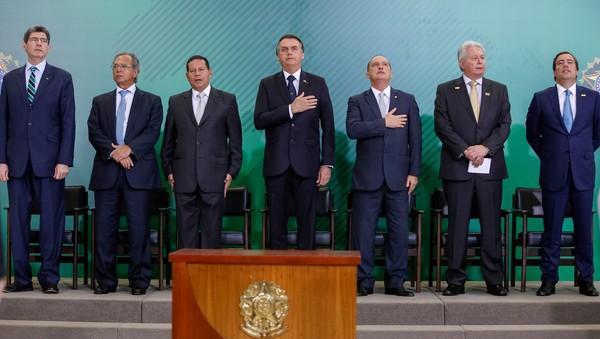 O presidente Jair Bolsonaro ao lado do vice-presidente, Hamilton Mourão (esq), e do ministro da Casa Civil, Onyx Lorenzoni (dir), durante posse de presidentes de bancos no Palácio do Planalto (Imagem: Divulgação)