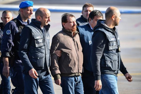 Cesare Battisti é escoltado nesta segunda-feira (14), após descer de avião que o trouxe da Bolívia até Roma, na Itália — Foto: Alberto Pizzoli / AFP